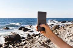 Man taking pictures of coastline Royalty Free Stock Photos