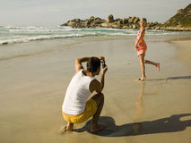 Man taking pictures of his girlfriend on the beach. Royalty Free Stock Photography