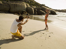 Man taking pictures of his girlfriend on the beach. Royalty Free Stock Photo