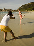 Man taking pictures of his girlfriend on the beach. Stock Image