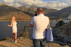 Man taking pictures of his girlfriend near the sea and mountains stock photo