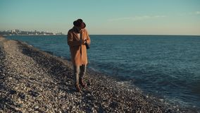 Man taking pictures of nature. Stylish man is walking on the beach with a camera wearing warm clothes. He is taking pictures of sea and beach stock footage