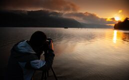 Free Man Taking Pictures Photographer Of A Sunrise Over A Lake Between The Mountains Stock Image - 200490731