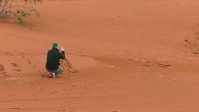 Man taking pictures in rain in Sahara desert stock video