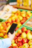 Man taking pictures with smartphone in supermarket Royalty Free Stock Photos