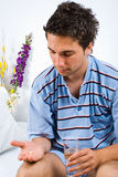 Man taking pill. Young man sitting on bed and holding pill in his hand prepare to taking with water,same series in Sick people Stock Images