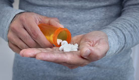 Man taking pills. Hands of man holding pill bottle with pills on hand Royalty Free Stock Photography