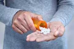 Man taking pills. Hands of man holding pill bottle with pills on hand Royalty Free Stock Photo