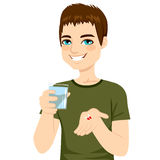 Man Taking Pills. Young attractive man taking pills with glass of water Royalty Free Stock Photo