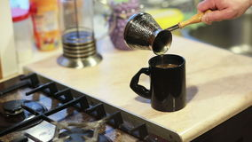 Man taking the pot and pouring coffee in a mug. Hands of a man taking the pot and pouring coffee in a mug stock video