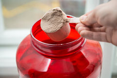 Man taking protein from container by the scoop. Man taking protein from container by the scoop Royalty Free Stock Photo