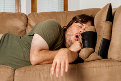 Man taking a quick nap on the couch Royalty Free Stock Images