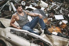 The man taking a rest. On a car wreck Stock Photo