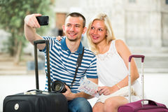Man taking self portrait. Smiling young men holding phone in hands and taking self portrait with girlfriend in city Stock Photography