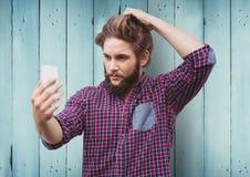 Man taking selfie against blue wood panel background. Digital composite of Man taking selfie against blue wood panel background royalty free stock images