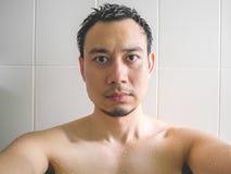 Man taking selfie in bathroom. Stock Image