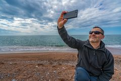 Man taking selfie on the beach. Caucasian man wearing sunglasses taking selfie with mobile phone on the beach in autumn royalty free stock photo