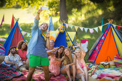 Man taking a selfie with friends at campsite. On a sunny day stock photo