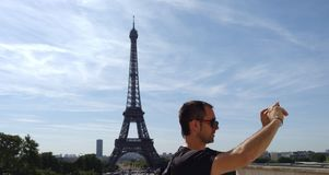 Man taking a selfie in front of Eiffel tower in Paris. France Royalty Free Stock Image
