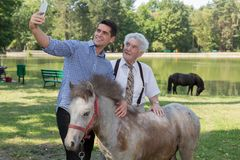 Man taking selfie with grandfather. Photo of men taking selfie with grandfather and ponytail stock photos