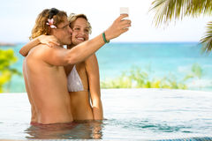 Man taking selfie and kissing his girlfriend Royalty Free Stock Photography