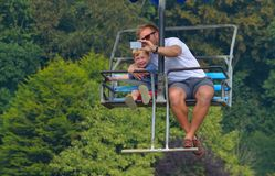 Man taking selfie with little boy while riding on a chair lift. Stock Photo