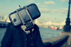 Man taking a selfie next to the River Thames in London, with a f Royalty Free Stock Images
