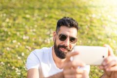 Man Taking a Selfie Outdoors. Hipster Young Man Taking a Selfie with his Mobile Phone in a Park - Using the Cellphone Outdoors in a Sunny Day of Summer royalty free stock images