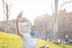 Man Taking a Selfie Outdoors. Hipster Young Man Taking a Selfie with his Mobile Phone in a Park - Using the Cellphone Outdoors in a Sunny Day of Summer stock images