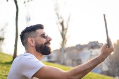 Man Taking a Selfie Outdoors. Hipster Young Man Taking a Selfie with his Mobile Phone in a Park - Using the Cellphone Outdoors in a Sunny Day of Summer royalty free stock photo