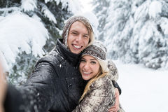 Man Taking Selfie Photo Young Romantic Couple Smile Snow Forest Outdoor. Winter Pine Woods stock photography