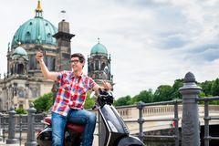 Man taking a selfie during sightseeing tour with Vespa. Tourist man, taking selfie during sightseeing tour with Vespa in Berlin Royalty Free Stock Photos