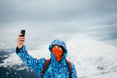Man taking selfie with smartphone on mountains background Royalty Free Stock Images
