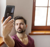 Man taking selfie. Young man is taking photo by himself in home Stock Images