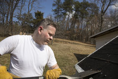 Man taking shingles off a shed roof Stock Image