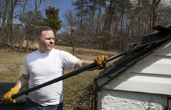 Man taking shingles off a shed roof Stock Photos