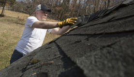 Man taking shingles off a shed roof Stock Photo