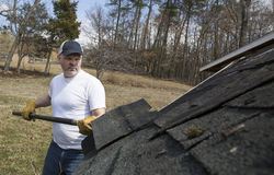 Man taking shingles off a shed roof Royalty Free Stock Photo