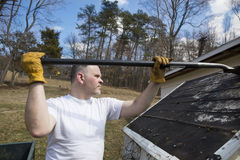 Man taking shingles off a shed roof Royalty Free Stock Photography
