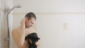 A man taking a shower with a black cat. close-up stock video