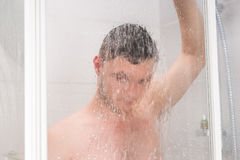 Man taking a shower and holding shower head behind misted glass. Man taking a shower and holding shower head while standing under flowing water behind Stock Images