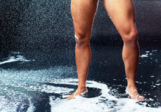 Man taking shower. Legs of a mucular young man taking shower Stock Image