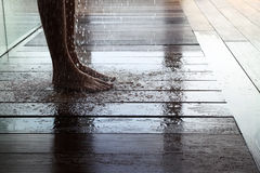 Man taking shower low section. Man standing on wet wooden floor taking shower in a wellness center Stock Image