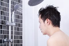 Man are taking a shower and washing face in bathroom. Man are taking a shower and washing face in the bathroom Royalty Free Stock Images