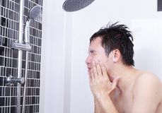 Man are taking a shower and washing face in bathroom. Man are taking a shower and washing face in the bathroom Stock Image