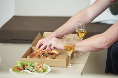 Man taking slice of pizza. Hands of men taking slice of pizza from the box on small table at home stock photo