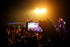 Man taking smart phone at live concert and lights on stage.  stock photo