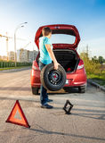Man taking spare wheel out of trunk. Photo of man taking spare wheel out of trunk Royalty Free Stock Images