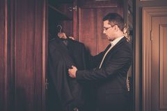 Man taking suit from wardrobe. Middle-aged man taking suit from wardrobe Stock Images