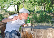 Man taking a swig of alcohol from a bottle. Man with a drinking problem sitting outdoors in a wooded park at a rustic table taking a swig of alcohol from a Royalty Free Stock Image